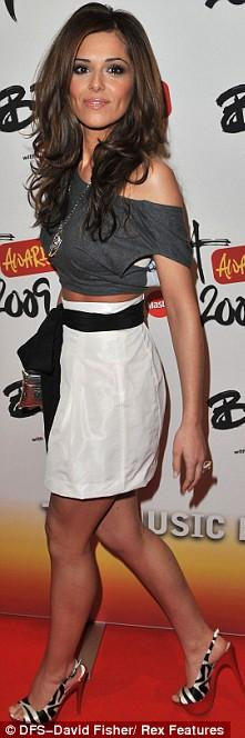 Cheryl teams her cropped tee with a high waisted skirt